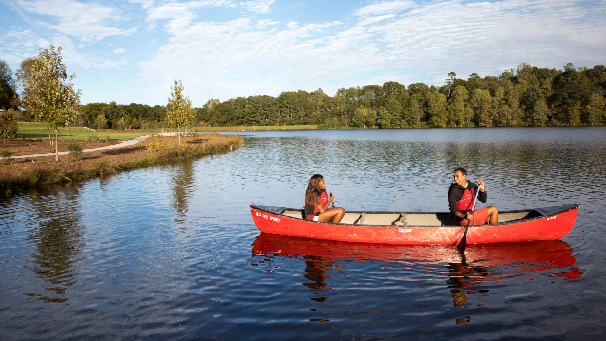 Two people smile at each other while paddling a canoe on a lake under a partly cloudy blue sky