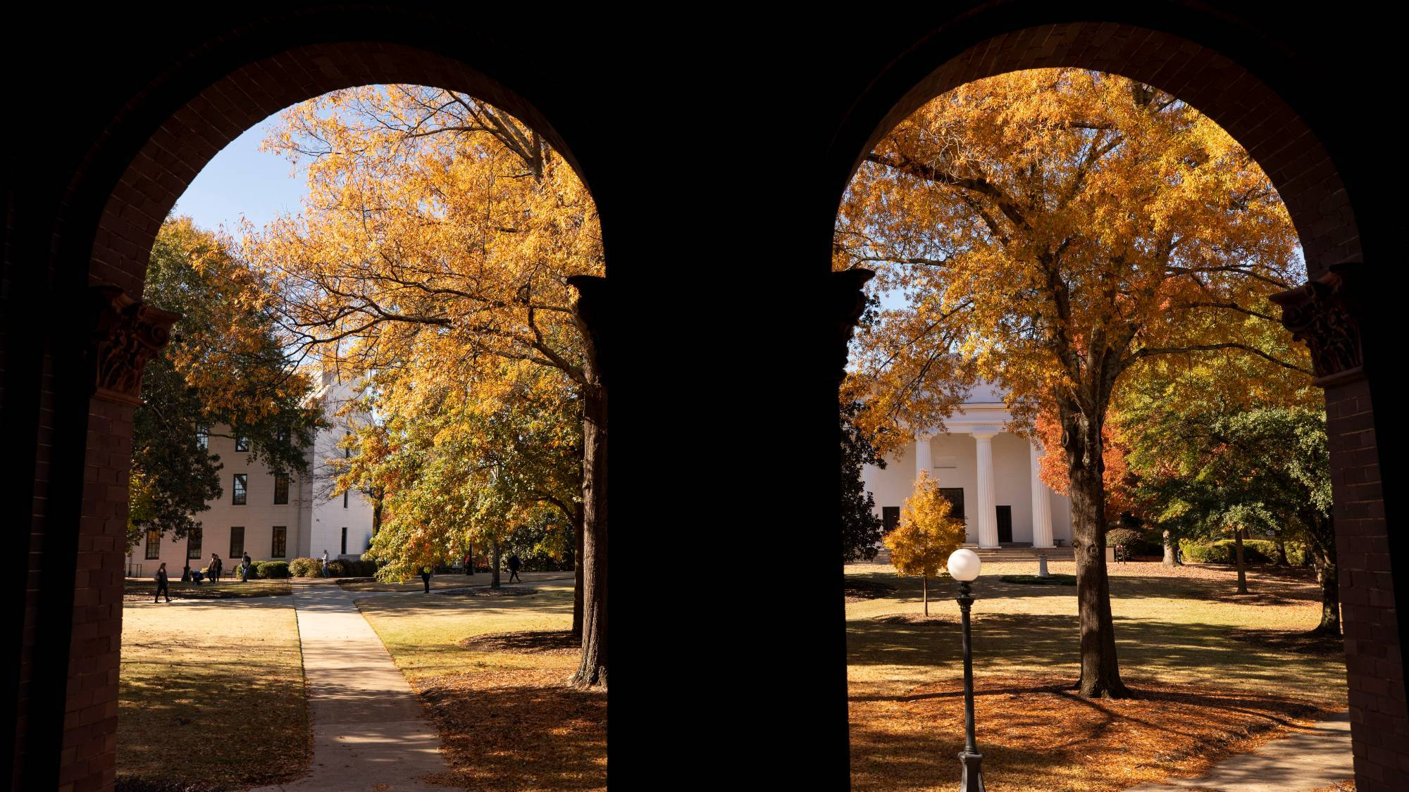 View through two brick archways to a campus quad in autumn
