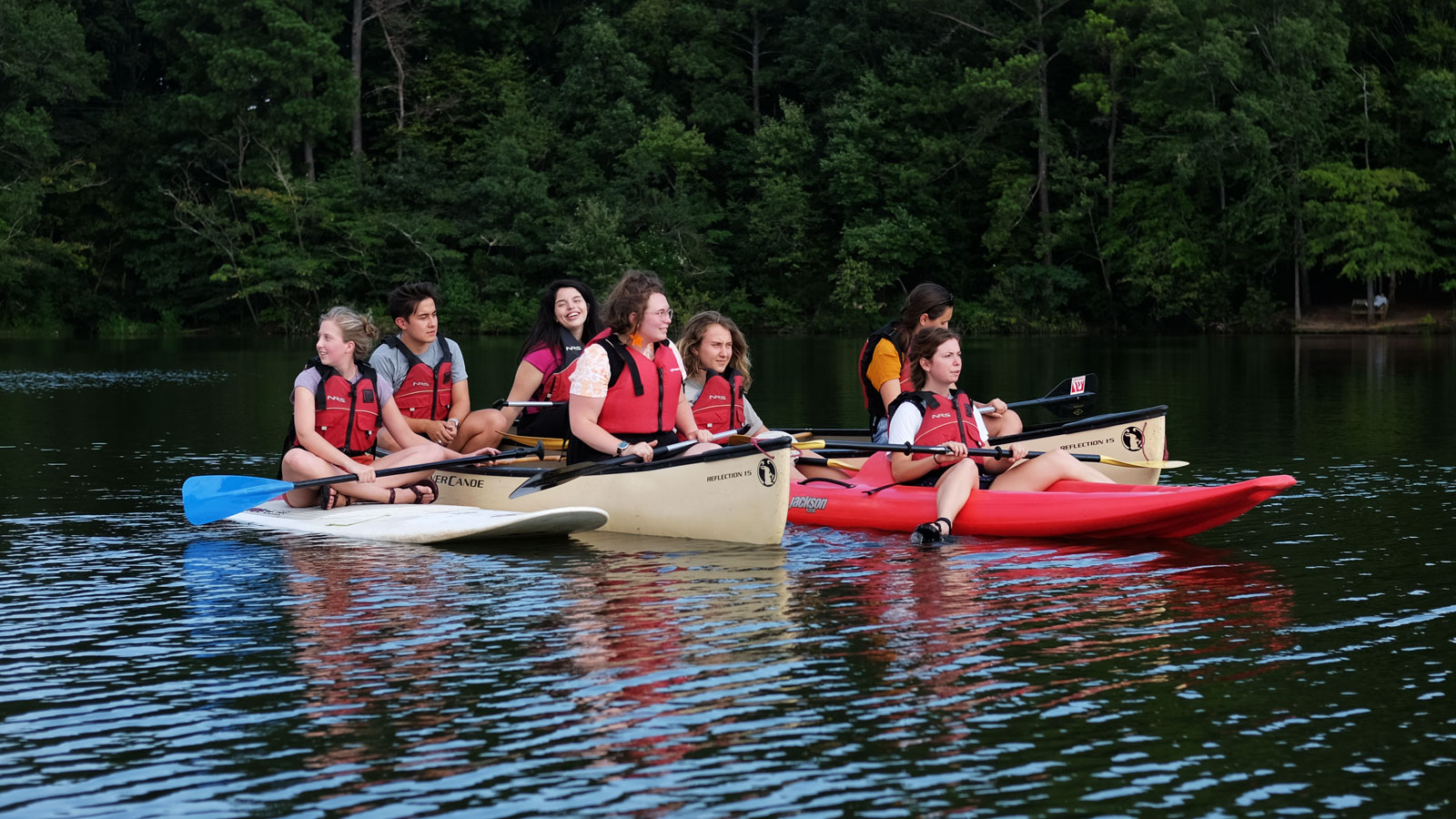 A group of students relax in canoes and kayaks on a lake.