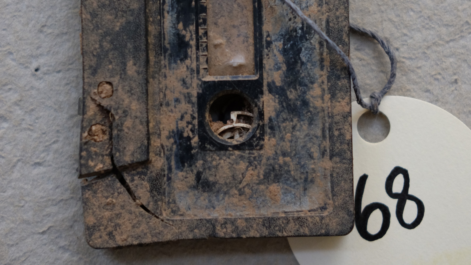 "Close up of a cassette tape caked in mud with a tag that says ""68"" attached to it"