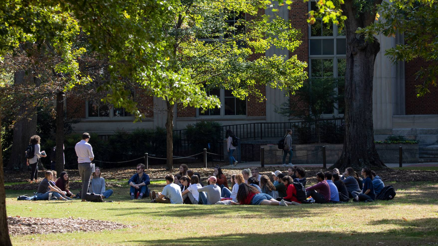 A professor stands and speaks to a group of students sitting or lying down on the grass