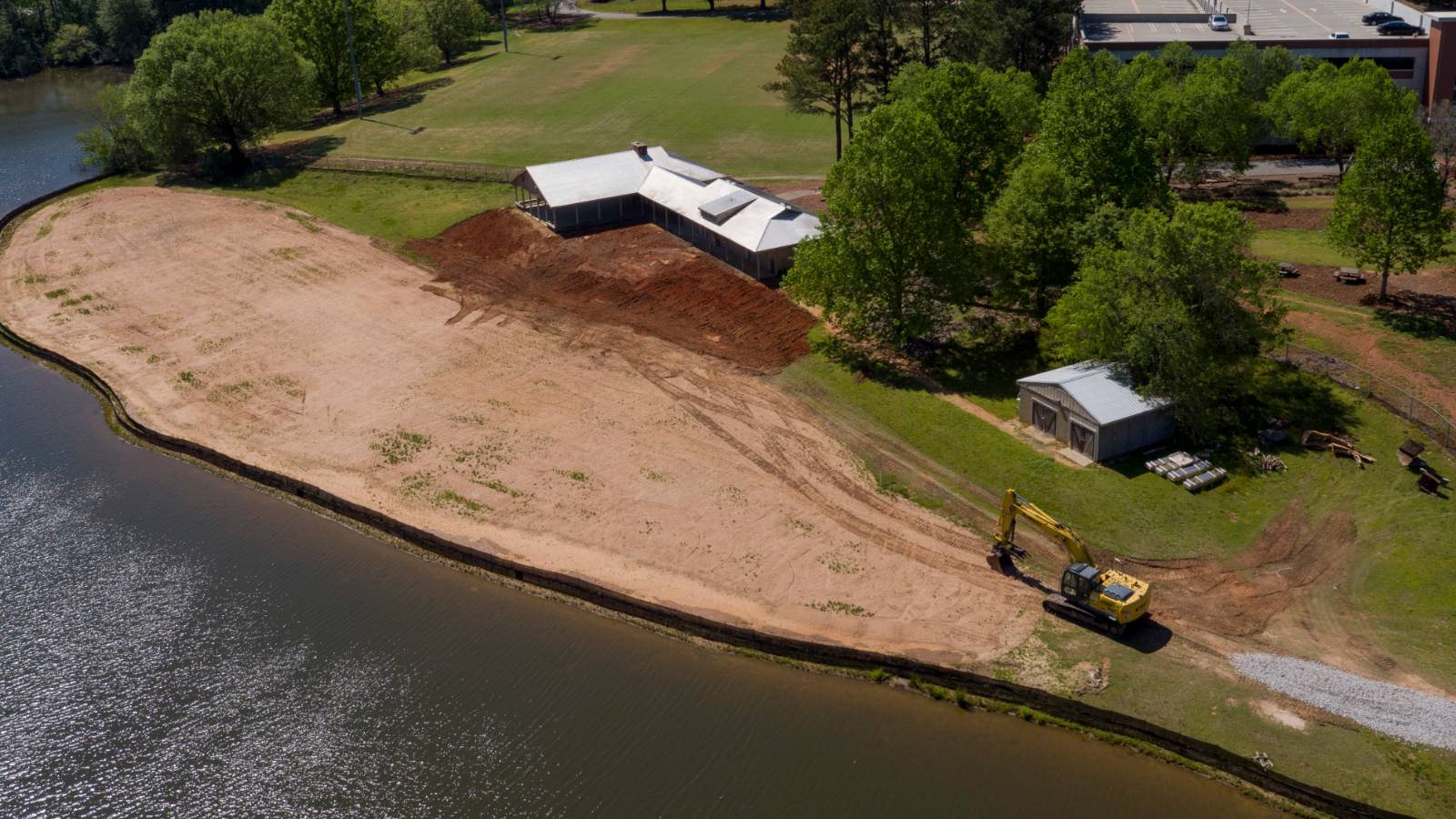 Aerial photo of a lakefront pavilion with construction equipment performing earthwork on the edge of the water