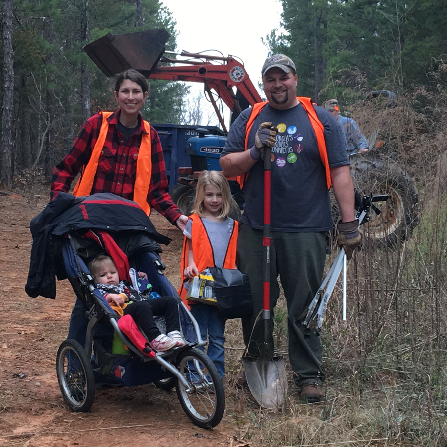 Photo of Andrew Saunders and his family outside at a volunteer cleanup event